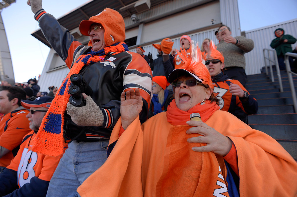 . Pam and Steve Clegg, from Cody, Wyoming, cheer for the Broncos in the upper section during the first quarter. The Denver Broncos take on the San Diego Chargers at Sports Authority Field at Mile High in Denver on January 12, 2014. (Photo by Craig F. Walker/The Denver Post)