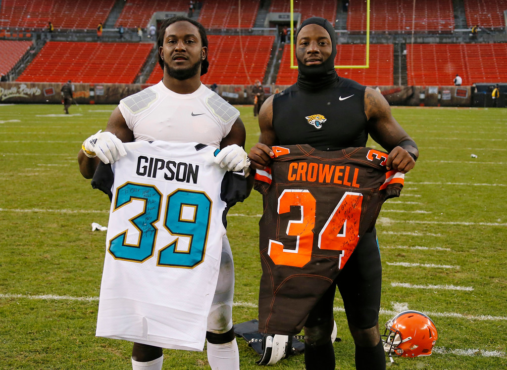 . Jacksonville Jaguars free safety Tashaun Gipson, right, and Cleveland Browns running back Isaiah Crowell hold up jersey\'s after an NFL football game, Sunday, Nov. 19, 2017, in Cleveland. (AP Photo/Ron Schwane)