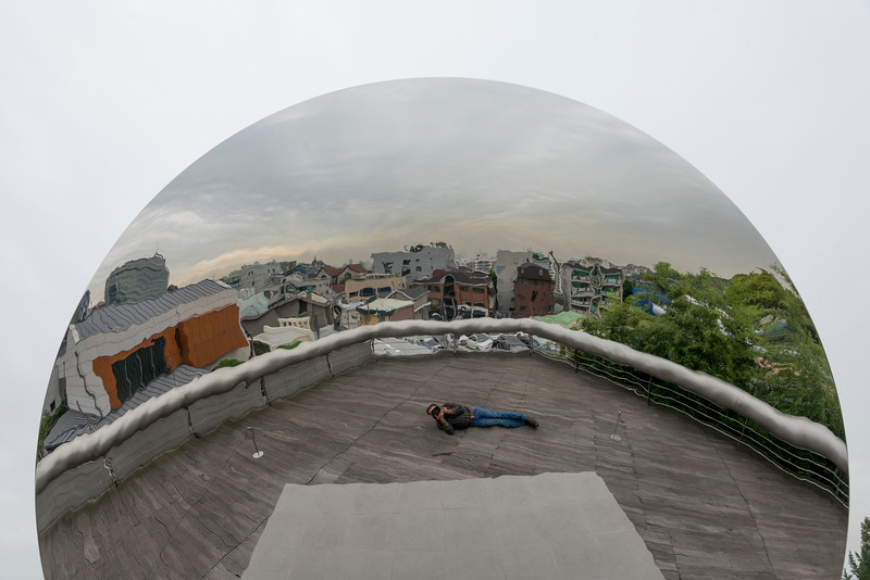 Reflection of photographer in the Sky Mirror sculpture by Anish Kapoor in the museum of Leeum, Samsung Museum of Art, Seoul, South Korea