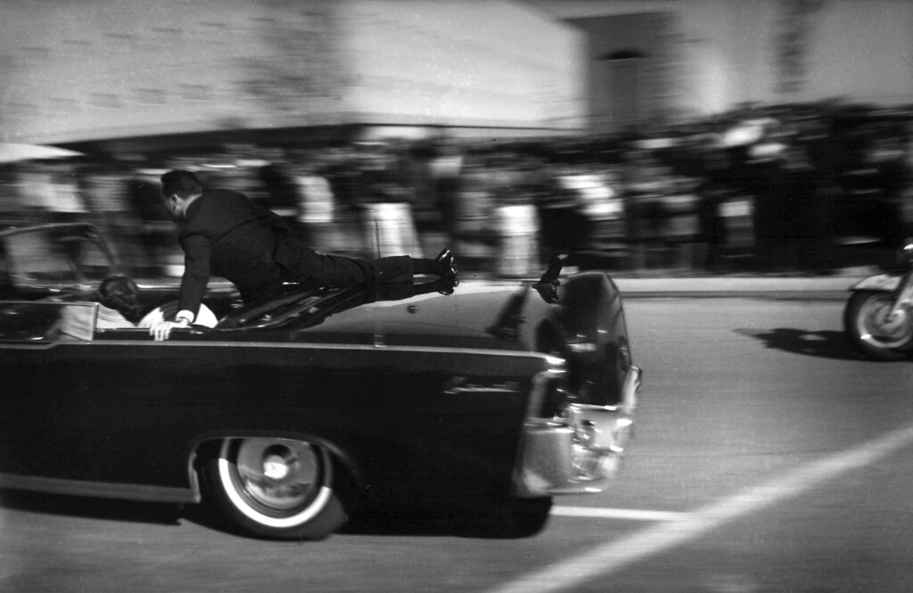 . The limousine carrying mortally wounded President John F. Kennedy races toward the hospital seconds after he was shot in Dallas, Tx., Nov. 22, 1963.  With secret service agent Clinton Hill riding on the back of the car, Mrs. John Connally, wife of the Texas governor, bends over her wounded husband, and Mrs. Kennedy leans over the president. (AP Photo/Justin Newman)