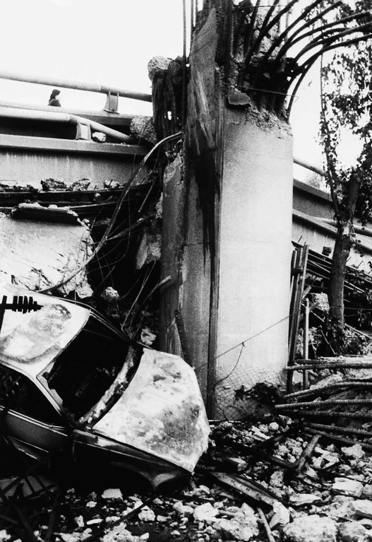 . A burned out vehicle lies at the base of a broken column that once supported two decks of the Cypress freeway, Oct. 18, 1989, Oakland, Calif. (AP Photo/Stuart Brinn)