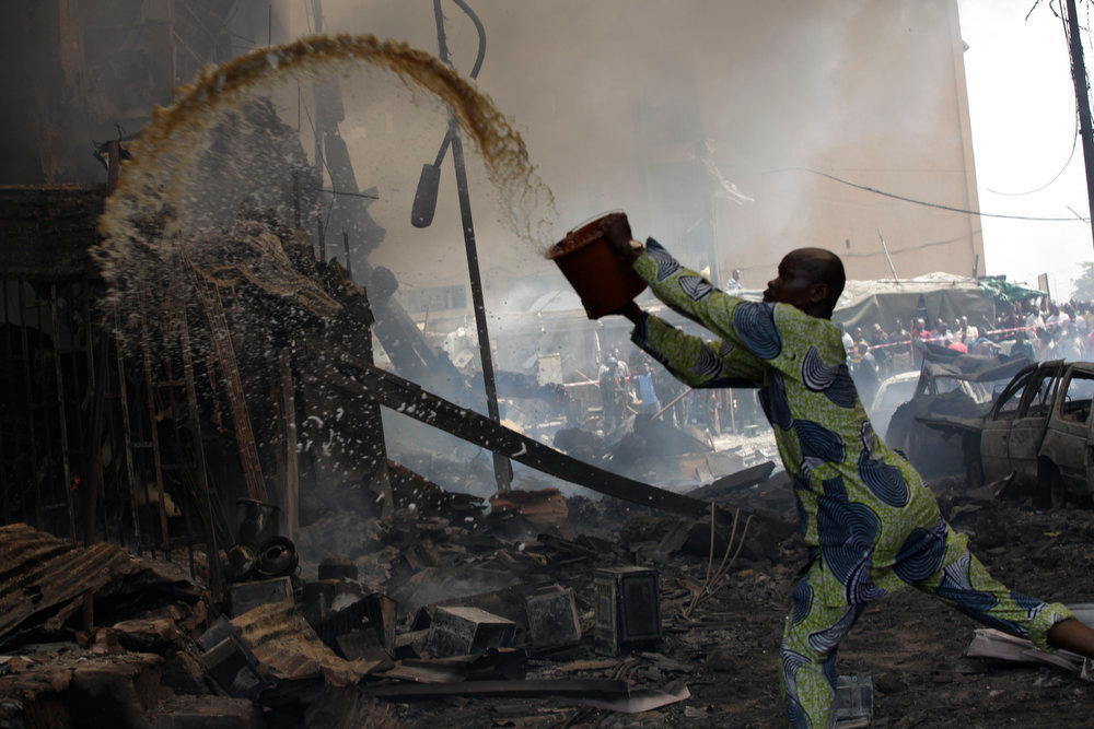Description of . A man tries to contain fire at a burnt out warehouse on Lagos Island in Lagos, Nigeria, Wednesday, Dec. 26, 2012. An explosion ripped through a warehouse Wednesday where witnesses say fireworks were stored in Nigeria's largest city, sparking a fire. It wasn't immediately clear if anyone was injured in the blast that firefighters and locals struggled to contain. (AP Photos/Sunday Alamba)