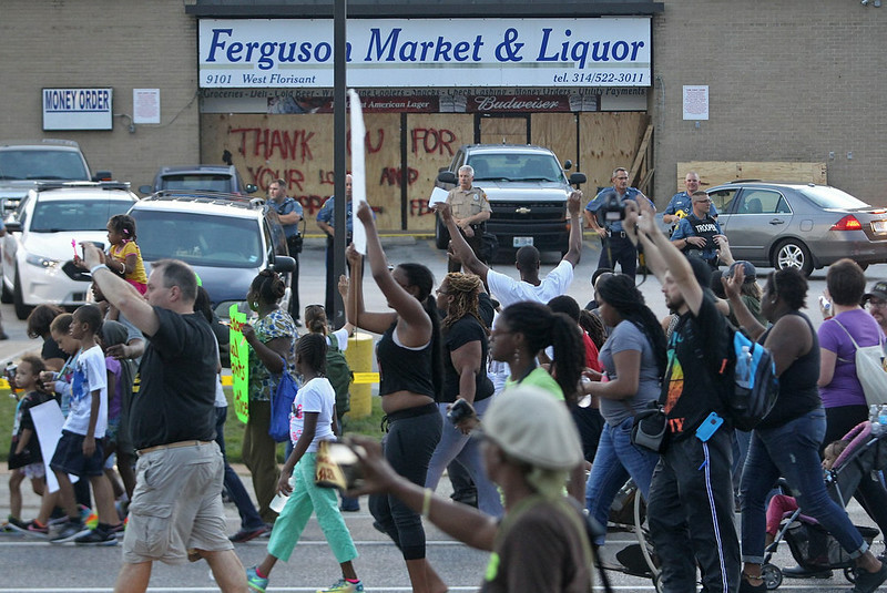 . Protesters march past the looted Ferguson Market & Liquor store on W. Florissant in Ferguson on Saturday afternoon, Aug. 16, 2014. The store has been looted twice in the past week. It is the store where Michael Brown was seen on surveillance video. (AP Photo/St. Louis Post-Dispatch, J.B. Forbes)