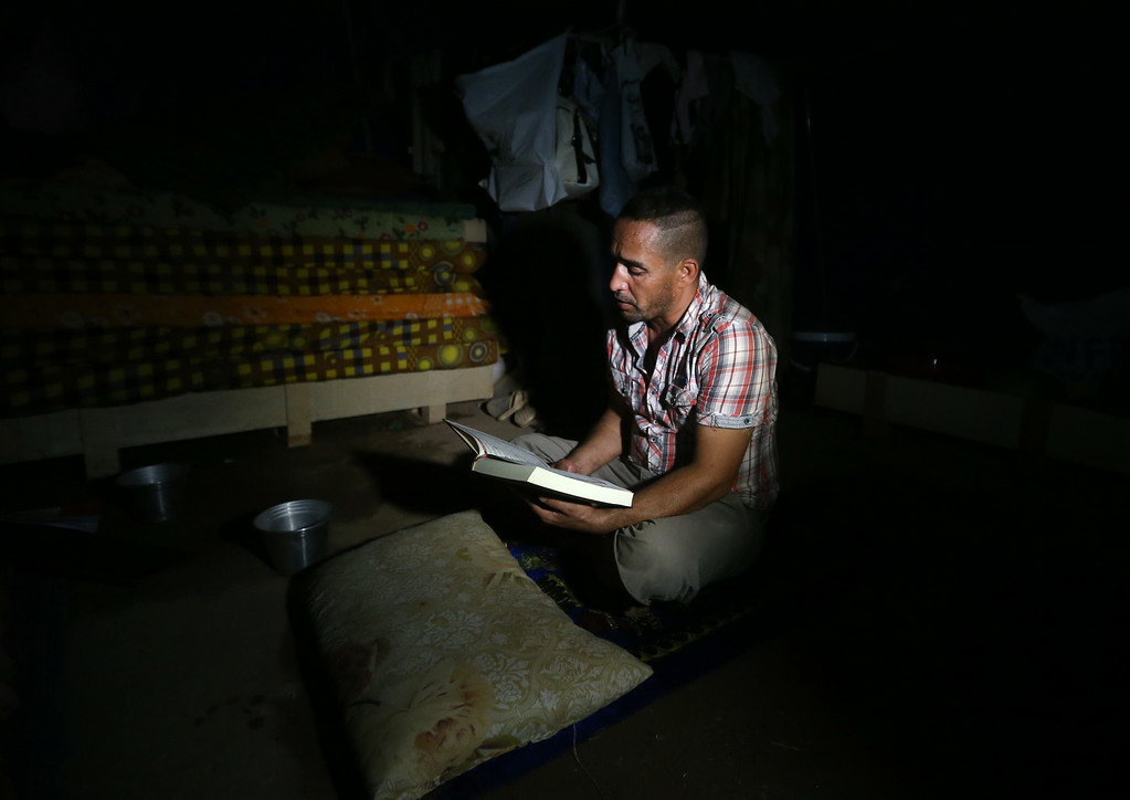. An Iraqi displaced man, Ammar Ahmad, 35, who fled with his family from the Iraqi northern city of Mosul, reads the Quran, Islam\'s holy book after he received it from a Kurdish local charity organization, a day before the starting of the Islamic holy month of Ramadan, at a camp for displaced Iraqis who fled from Mosul and other towns, in Khazer area outside Irbil north Iraq, Saturday, June 28, 2014. Ammar a Sunni man said that he can\'t go back to Mosul after he threatened to be killed by al-Qaida-inspired Islamic State in Iraq and the Levant (ISIL) because he married from a Shiite woman. Across a wide belt that stretches halfway around the globe, the worldís estimated 1.6 billion Muslims will mark the beginning of Ramadan this weekend. The holy season is marred by unprecedented turmoil, violence and sectarian hatreds that threaten to rip apart the Middle East, the epicenter of Islam. (AP Photo/Hussein Malla)