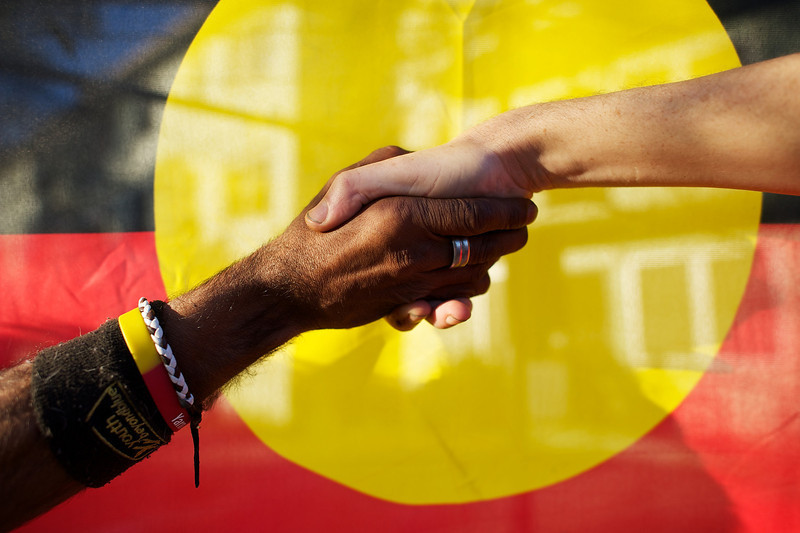 Indigenous and Non-Indigenous Australian shaking hands in front of the Aboriginal Flag