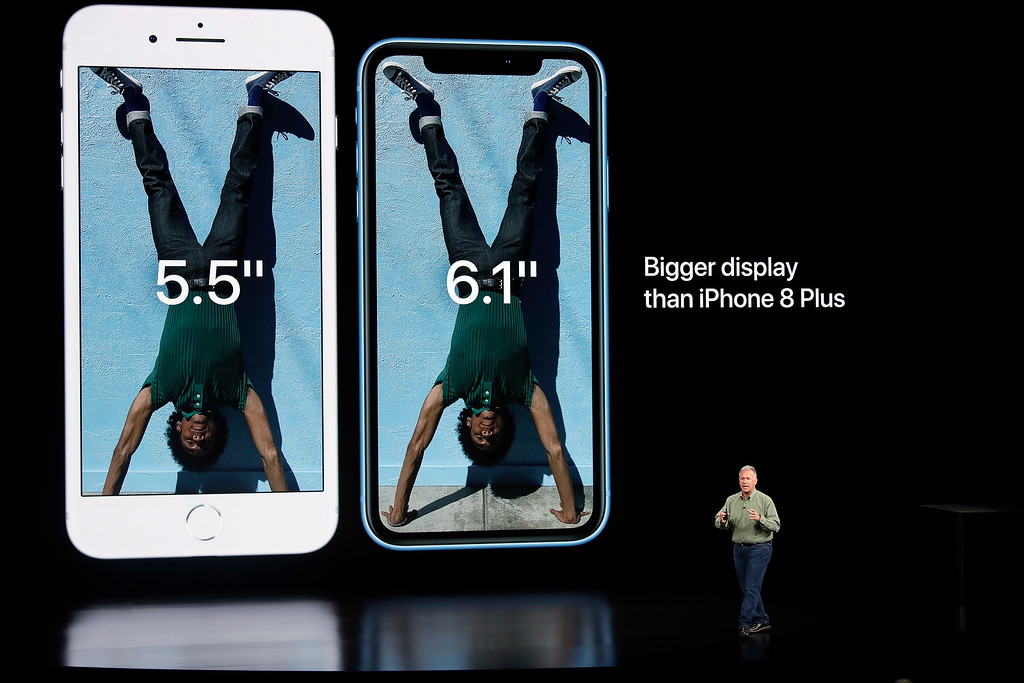. Phil Schiller, Apple\'s senior vice president of worldwide marketing, right, shows the size differences on new iPhones during an event to announce new products Wednesday, Sept. 12, 2018, in Cupertino, Calif. (AP Photo/Marcio Jose Sanchez)