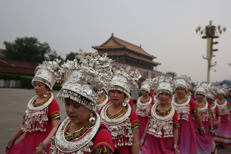 . A chorus\' members dressed in ethnic minority traditional costume visit the Tiananmen Square on June 4, 2013 in Beijing, China.  (Photo by Feng Li/Getty Images)