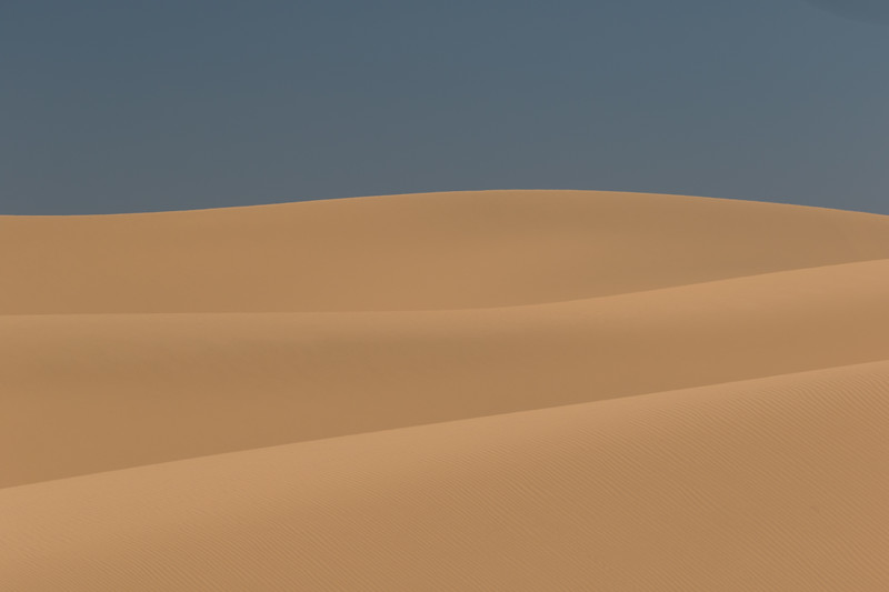Smooth sand dunes over lap each other in a sensual pattern