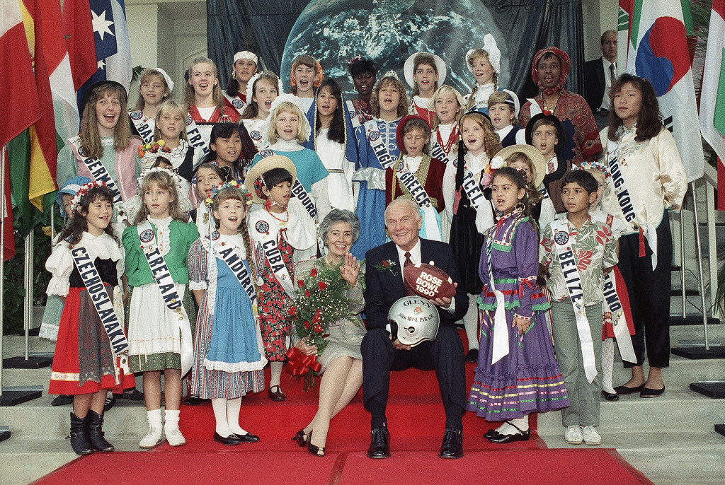 ". Sen. John Glenn (D-Ohio) and his wife, Annie, are surrounded by youngsters representing different countries of the world after he was named Grand Marshal of the 101st Rose Parade in Pasadena, California, Thursday, Oct. 12, 1989. The theme of the parade is ""A World of Harmony.\"" Glenn was the first American to orbit the earth. (AP Photo/Nick Ut)"