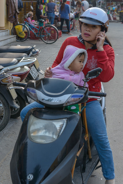 Mom pauses to take a call. It is very common to see quite young children riding with their parents.