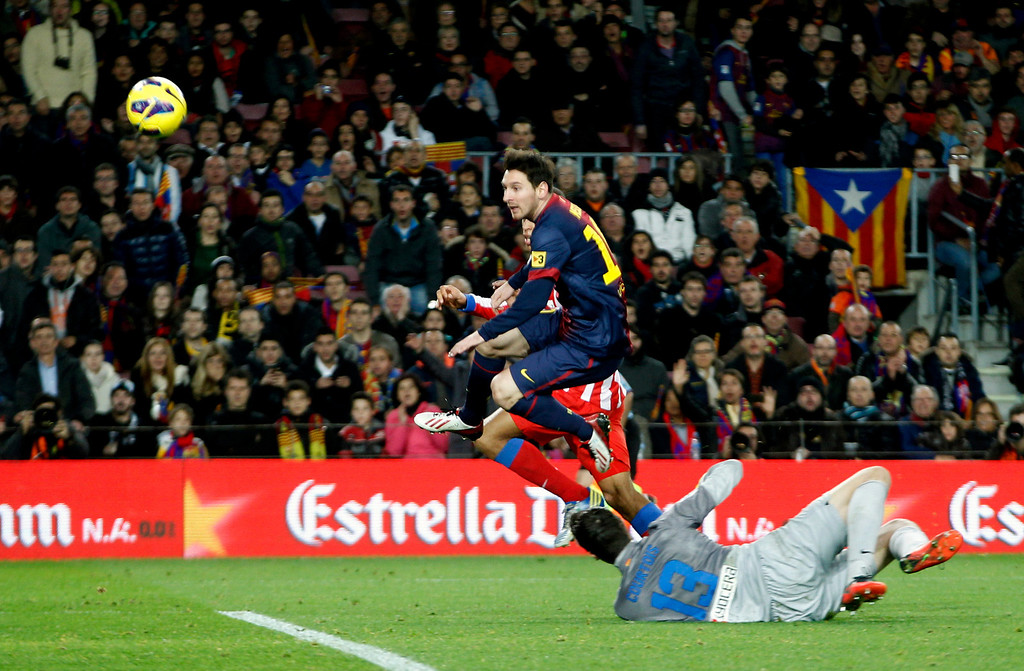 . Barcelona\'s Lionel Messi (top) scores his second goal against Atletico de Madrid goalkeeper Thibaut Courtois during their Spanish first division soccer match at Nou Camp stadium in Barcelona December 16, 2012.     REUTERS/Gustau Nacarino