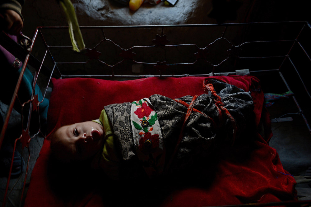 Description of . An internally displaced Afghan child rests in a cradle inside mud shelter in a makeshift camp as winter approaches in Kabul on December 4, 2012. The country has nearly half a million displaced people, many living in primitive camps where the cold weather will mean uncertainty for some. SHAH MARAI/AFP/Getty Images