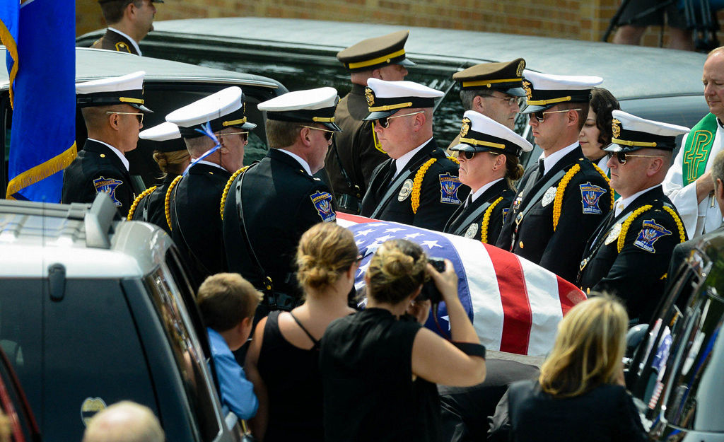 . Officer Patrick\'s casket is lifted by an honor guard as it is placed in a hearse outside St. Stephen\'s.  (Pioneer Press: Ben Garvin)