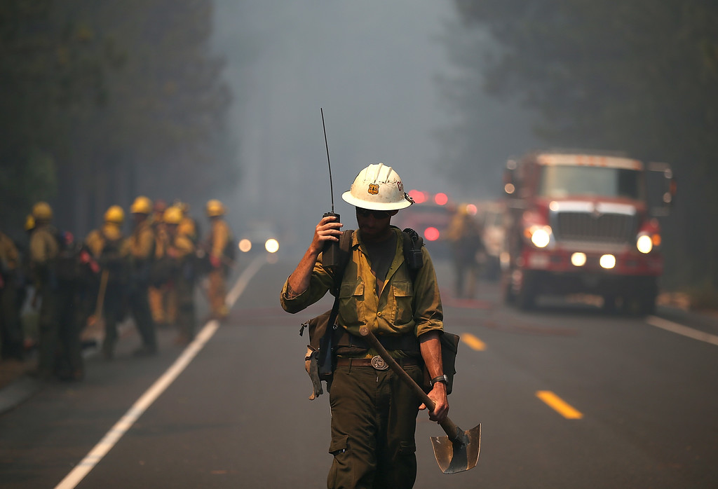 . GROVELAND, CA - AUGUST 22:  A U.S. Forest Service firefighter monitors a radio while battling the Rim Fire on August 22, 2013 in Groveland, California. The Rim Fire continues to burn out of control and threatens 2,500 homes outside of Yosemite National Park. Over 1,000 firefighters are battling the blaze that was reduced to only 2 percent containment after it nearly tripled in size overnight.  (Photo by Justin Sullivan/Getty Images)
