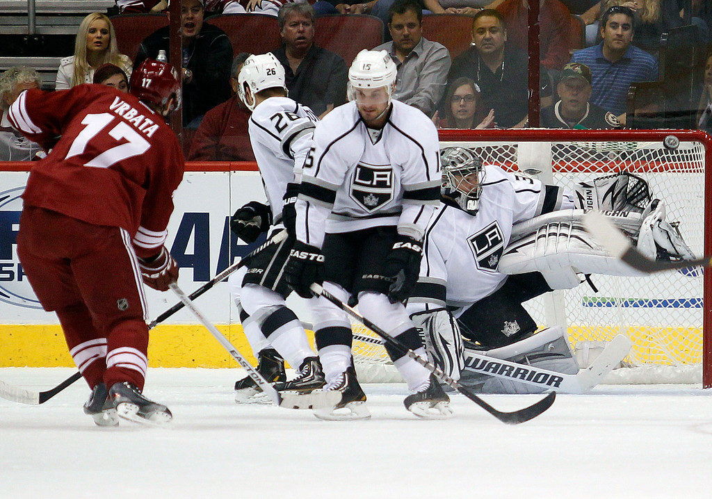 . Los Angeles Kings goalie Jonathan Qucik (32) makes a kick save on a shot from Phoenix Coyotes right winger Radim Vrbata (17) of the Czech Republic, as Kings defenders Slava Voynov (26) of Russia, and Brad Richardson (15) step up in front of Quick  in the first period of an NHL hockey game Tuesday, April 2, 2013, in Glendale, Ariz. (AP Photo/Paul Connors)