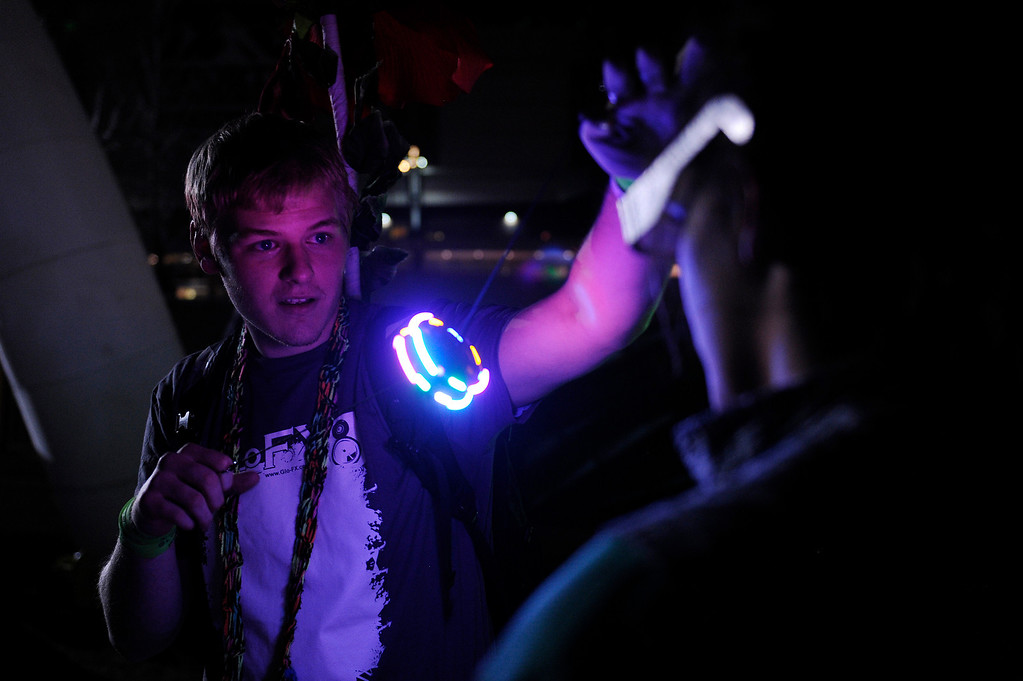 . DENVER, CO - APRIL 4: Grant Milford, of Manhattan, Kansas, demonstrates a string of lights for a fellow fan as Knife Party  performs during the Snowball Music Festival at Sports Authority Field at Mile High Stadium on April 4, 2014 in Denver, Colorado. The Snowball Music Festival is celebrating its first year in Denver after spending the previous three years as a mountain based festival. (Photo by Seth McConnell/The Denver Post)