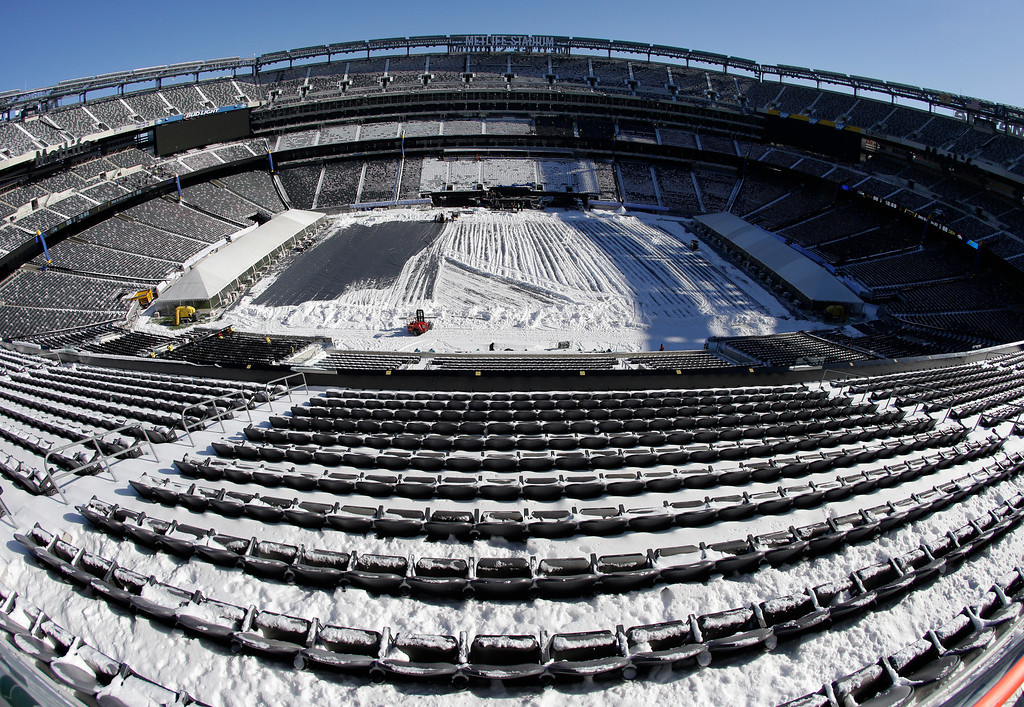 . In this photograph taken with a fisheye lens, snow is accumulated on the seats and on the field of MetLife Stadium as crews removed snow ahead of Super Bowl XLVIII following a snow storm, Wednesday, Jan. 22, 2014, in East Rutherford, N.J.  (AP Photo/Julio Cortez)