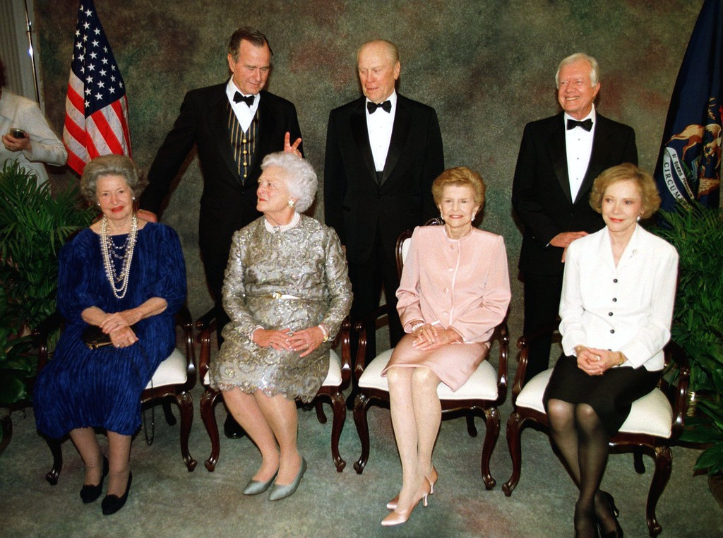 . Former President George Bush makes rabbit ears behind his wife, Barbara, as former presidents and first ladies wait for the official portrait during a gala Wednesday night, April 16, 1997, in Grand Rapids, Mich., in honor of the rededication of the Ford Museum. Front row from left are Lady Bird Johnson, Barbara Bush, Betty Ford, and Rosalynn Carter. Back row from left are former Presidents George Bush, Gerald Ford, and Jimmy Carter. (AP Photo/Carlos Osorio)