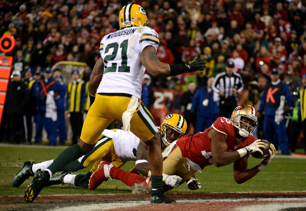 Description of . Wide receiver Michael Crabtree #15 of the San Francisco 49ers catches a touchdown pass thrown by quarterback Colin Kaepernick #7 against the Green Bay Packers in the second quarter during the NFC Divisional Playoff Game at Candlestick Park on January 12, 2013 in San Francisco, California.  (Photo by Harry How/Getty Images)