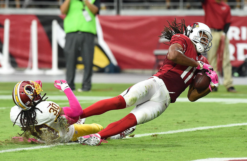 . Wide receiver Larry Fitzgerald #11 of the Arizona Cardinals is hit in the end zone by cornerback E.J. Biggers #30 of the Washington Redskins during the second half against of the NFL game at University of Phoenix Stadium on October 12, 2014 in Glendale, Arizona.  (Photo by Norm Hall/Getty Images)