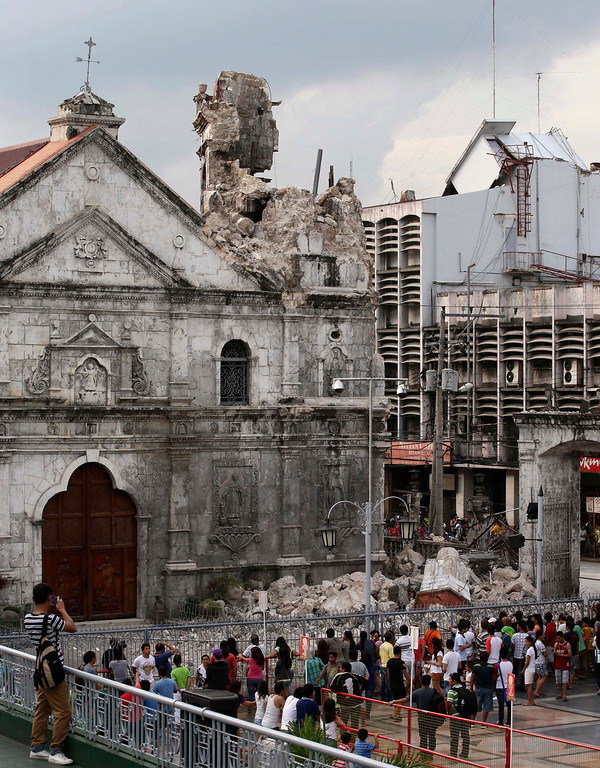. Residents look at the Basilica De Sto. Nino, or Basilica of the Holy Child, following a 7.2-magnitude earthquake that hit Cebu city in central Philippines Tuesday Oct. 15, 2013. (AP Photo/Bullit Marquez)