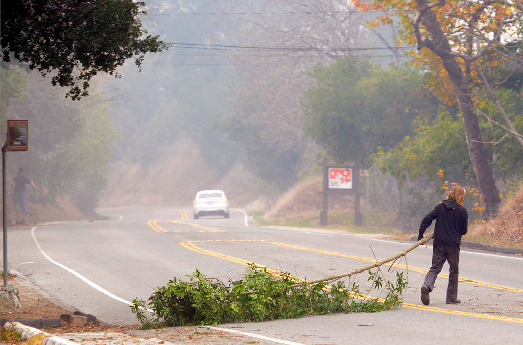 . A man pulls tree trimmings across Highway 1 while clearing fuel around structures as firefighters battle a wildland fire in the Pfeiffer Ridge area in Big Sur, Calif. on Tuesday December 17, 2013. (Photo David Royal/ Monterey County Herald)