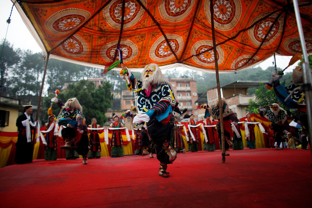 . Tibetan students perform a traditional dance during celebrations to mark the birthday of their spiritual leader the Dalai Lama in Katmandu, Nepal, Saturday, July 6, 2013. The Tibetan leader turned 78 today. (AP Photo/Niranjan Shrestha)