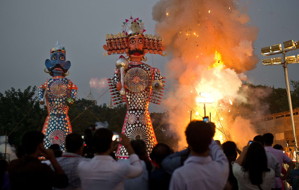 . Fireworks-laden effigies of the Hindu demon king Ravana (C), his brother Kumbhkuram (R), and son Meghanad, are set alight as Hindu devotees gather for their burning at dusk during the Hindu festival of Dussehra in New Delhi on October 13, 2013. Dussehra, which is celebrated at the end of the Navratri (nine nights) festival, symbolises the victory of good over evil in Hindu mythology. On the night of Dussehra fire-cracker stuffed effigies of demon king Ravana are set ablaze across the country.    PRAKASH SINGH/AFP/Getty Images