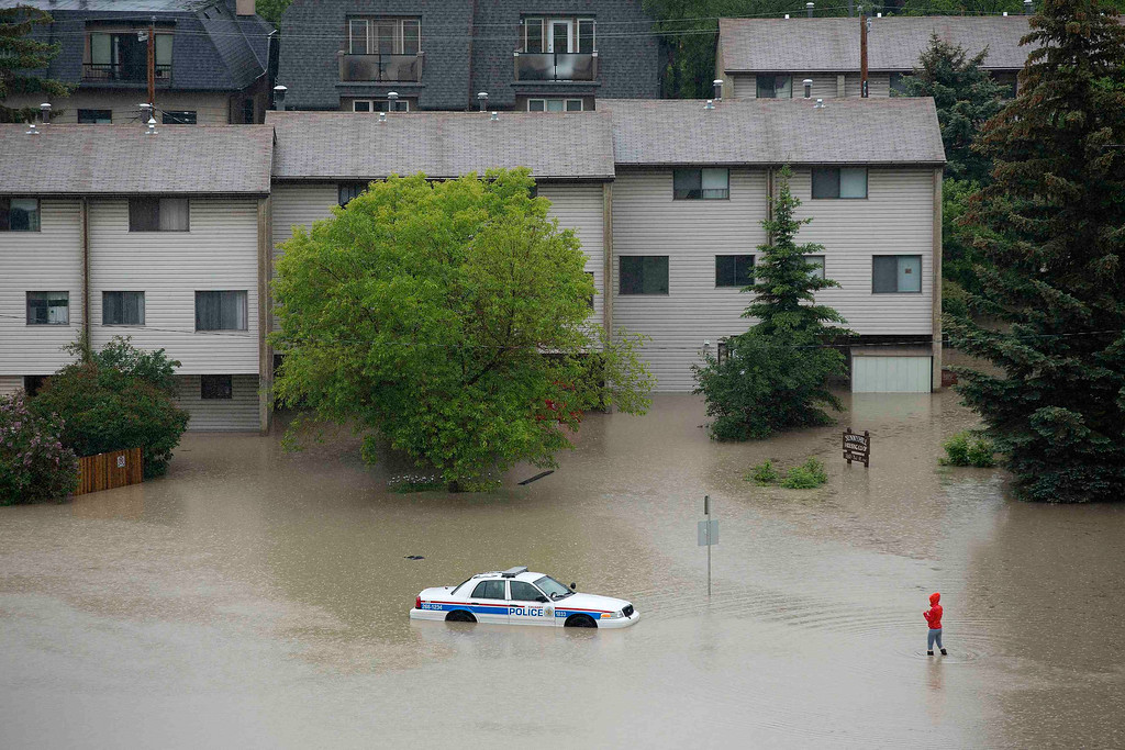 . A woman looks at an abandoned and partially submerged police car after flooding from the Bow River hit the neighborhood of Sunnyside in Calgary, Alberta June 21, 2013. REUTERS/Todd Korol