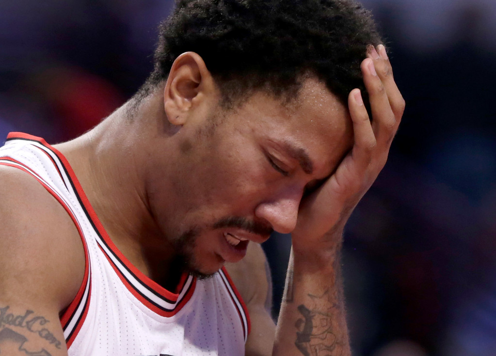 . Chicago Bulls guard Derrick Rose holds his head after being fouled during the second half of an NBA basketball game against the Detroit Pistons Monday, Nov. 10, 2014, in Chicago. The Bulls won 102-91. (AP Photo/Charles Rex Arbogast)