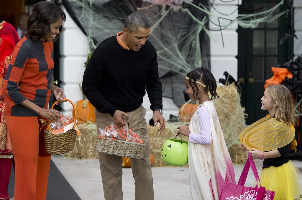 . US President Barack Obama and First Lady Michelle Obama hand out treats to local children and children of military families as they trick-or-treat for Halloween on the South Lawn of the White House in Washington, DC, October 31, 2013. SAUL LOEB/AFP/Getty Images
