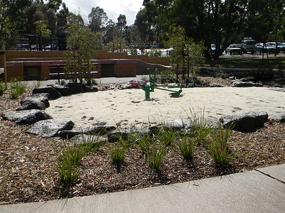naturalistic sandpit with boulder edging and digger