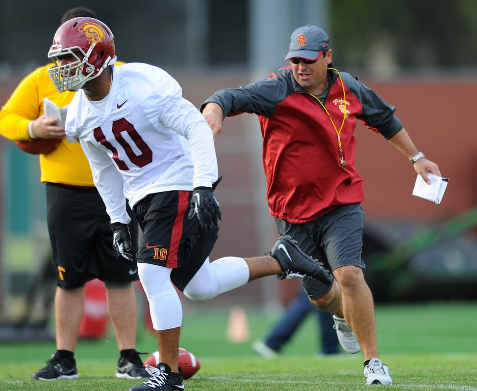 . USC head coach Steve Sarkisian chases off LB Hayes Pullard who crashed the offensive units drills at spring practice, Tuesday, March 11, 2014, at USC. (Photo by Michael Owen Baker/L.A. Daily News)