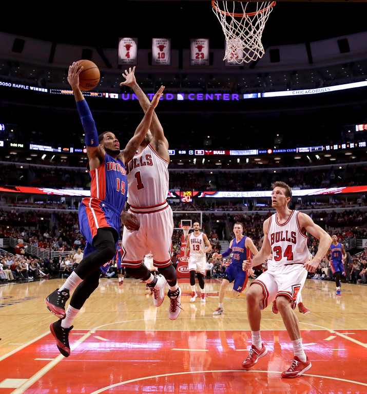 . Detroit Pistons guard D.J. Augustin (14) drives past Chicago Bulls guard Derrick Rose (1) as Mike Dunleavy (34) watches during the second half of an NBA basketball game Monday, Nov. 10, 2014, in Chicago. The Bulls won 102-91. (AP Photo/Charles Rex Arbogast)