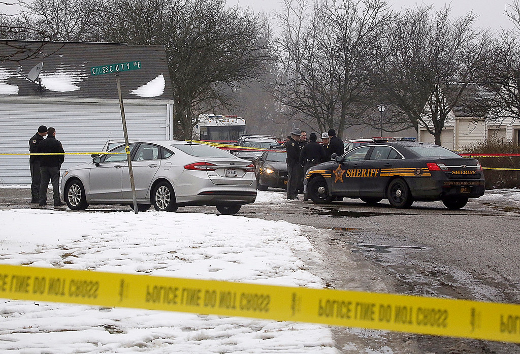 . Authorities investigate the scene of a shooting where two Westerville, Ohio, police officers were shot and killed responding to a hang-up 911 call, on Saturday, Feb. 10, 2018. Officers Eric Joering and Anthony Morelli were shot around noon after entering the residence in the Columbus suburb. (Tom Dodge/The Columbus Dispatch via AP)