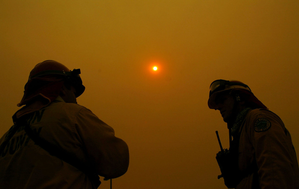 . SAN DIEGO - OCTOBER 27:  A pair of  firefighters from Marin County Fire Department talk to each other as the sun is obscured by the ash clouds at the Cedar Fire October 27, 2003 near Lakeside in San Diego, California. The death toll stands at 13, with more than 1,000 homes being reduced to ashes as southern California fires continue to burn. Winds have eased a bit, but 30,000 homes remain threatened by the fires, which have charred more than 400,000 acres, according to officials. Davis, who has activated the National Guard, predicted damages will be in the billions of dollars.  (Photo by Donald Miralle/Getty Images)