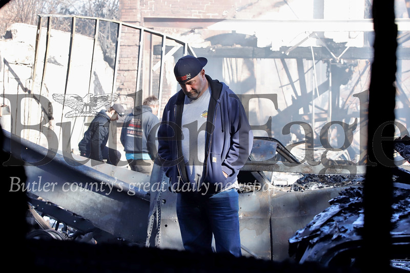 """Rob Goupil looks through the ashes of the workshop  space he and friend Joe Sharon rented to work on classic cars. Sharon called it a """"man cave"""" workshop. Their cars were spared from the initial fire Friday night that destroyed the old glass factory building. A second fire sparked Saturday morning destroying a secondary building containing a number of restored cars, car parts and mechanic tools. Seb Foltz/Butler Eagle"""