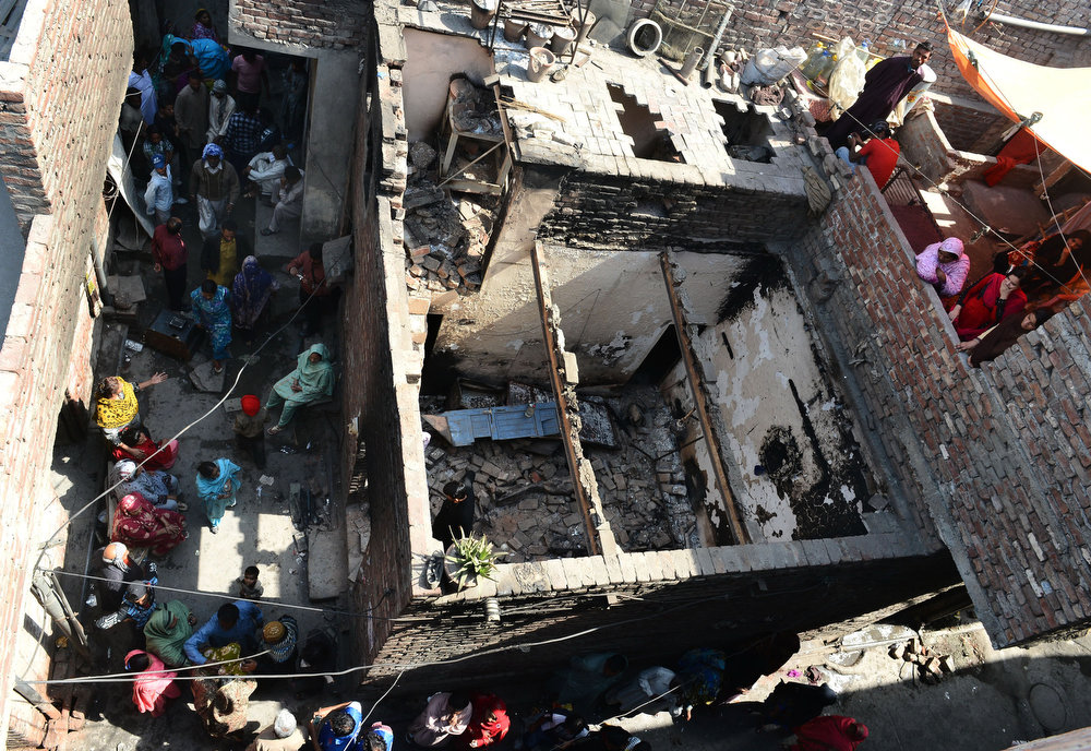 . Pakistani Christians gather around their burnt out homes torched by Muslim demonstrators in Lahore on March 10, 2013. Christians demonstrated around Pakistan to protest after a Muslim mob torched more than 100 Christian homes following allegations of blasphemy. More than 3,000 Muslims rampaged through Joseph Colony, a Christian area of the eastern city of Lahore, on March 9 after allegations that a Christian had made derogatory remarks about the Prophet Mohammed three days earlier. Arif Ali/AFP/Getty Images
