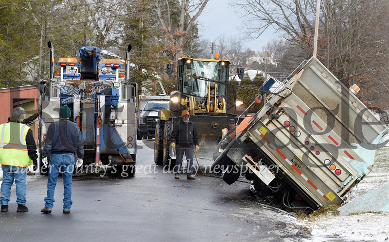 Harold Aughton/Butler Eagle: A towtruck driver pulls a Jefferson Twp. municipality truck out of a ditch after it flipped on its side while salting the road Wednesday, January 8, 2020.