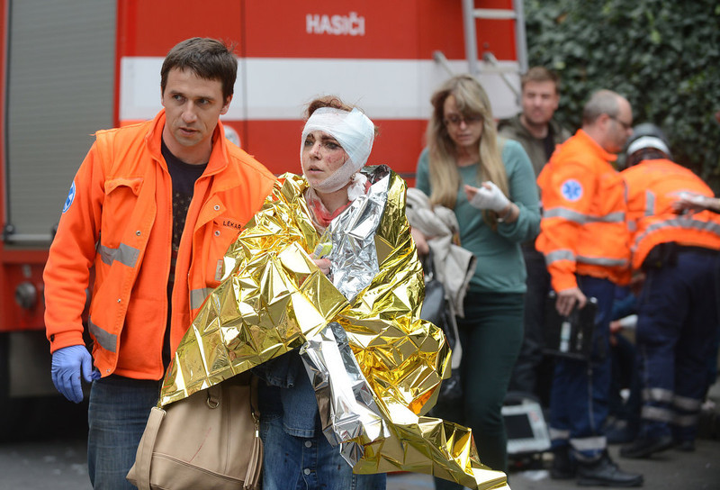 . Rescue workers help a woman who was injured in a blast next to the building where an explosion happened on April 29, 2013 in Prague, Czech Republic. Up to 20 people were injured in the blast in a multistory house in the historic centre of Prague, rescuers said. The police have sealed off the area popular with tourists and evacuated people from several houses.     MICHAL CIZEK/AFP/Getty Images