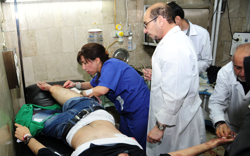 . Medics help a man who is injured after mortar bombs landed on the canteen of Damascus University\'s College of Architecture March 28, 2013 in this handout photograph distributed by Syria\'s national news agency SANA. Twelve Syrian students were killed on Thursday when rebel mortar bombs landed on the canteen of Damascus University\'s College of Architecture, state-run media said. Al-Ikhbariya television showed images of doctors pumping the chests of at least two young men and blood splattered on the floor of what appeared to be an outdoor canteen. REUTERS/SANA/Handout