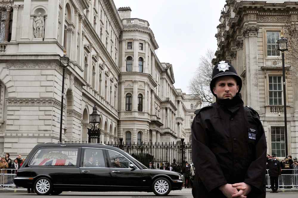 . A policeman stands guard as The hearse makes it way past Downing Street during the Ceremonial funeral of former British Prime Minister Baroness Thatcher at Downing Street on April 17, 2013 in London, England. Dignitaries from around the world today join Queen Elizabeth II and Prince Philip, Duke of Edinburgh as the United Kingdom pays tribute to former Prime Minister Baroness Thatcher during a Ceremonial funeral with military honours at St Paul\'s Cathedral. Lady Thatcher, who died last week, was the first British female Prime Minister and served from 1979 to 1990.  (Photo by Gareth Cattermole/Getty Images)
