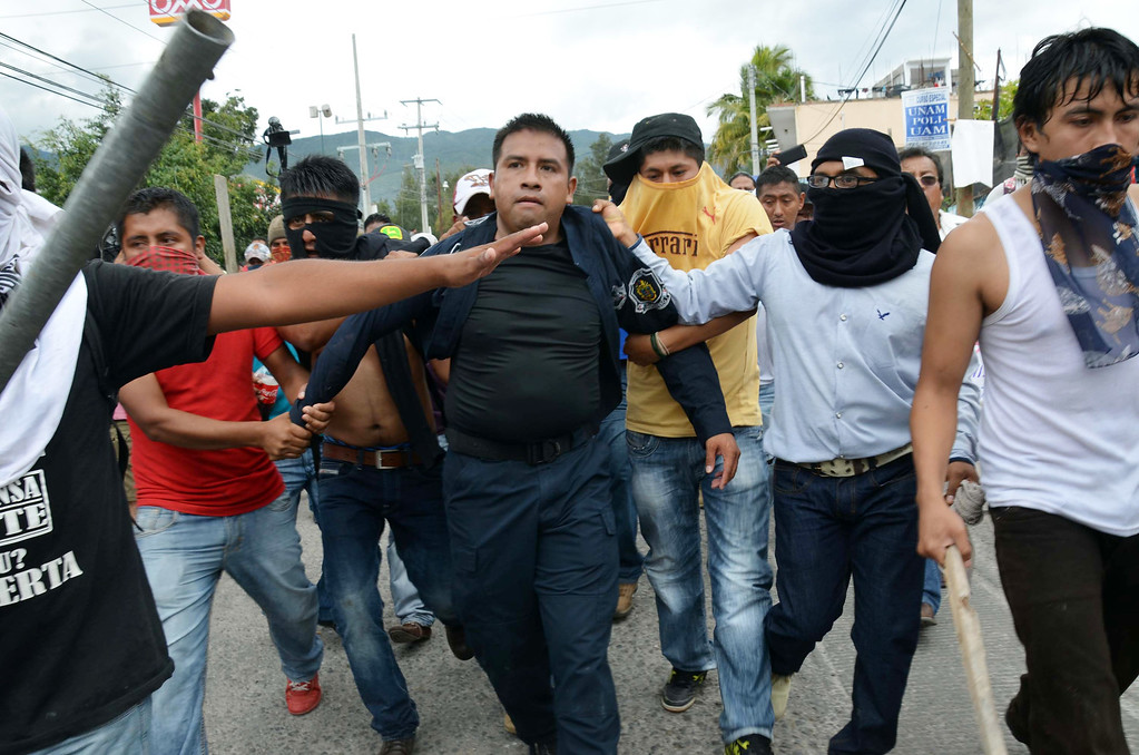 . Teachers detain a police during a clash with riot police in Chilpancingo, Mexico, Tuesday, Nov. 11, 2014. Supporters of the missing 43 college rural students, refusing to believe they are dead, have kept up the protests that have blocked major highways and set government buildings ablaze in recent weeks. (AP Photo/Alejandrino Gonzalez)