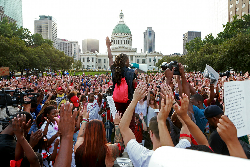. Jay Mitchell, of Pagedale, Mo., speaks and solicits a response of hands in the air from the crowd Thursday, Aug. 14, 2014, in St. Louis during a peace vigil and moment of silence for Michael Brown, an unarmed teenager who was shot and killed by Ferguson, Mo., police Saturday. Vigils have been held across the country for people who died at the hands of police. (AP Photo/St. Louis Post-Dispatch, Christian Gooden)