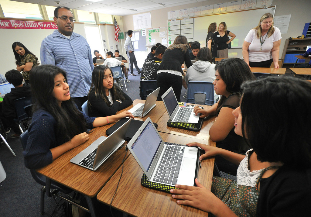 . Students ask questions of biology teacher Miguel Espinoza as they work with their laptops as part of the CORE program at Nogales High School in Rowland Heights on Wednesday September 18, 2013. CORE, the Creation Of Revolutionary Education, is a program that provides a small learning community centered around Technology, Science and English. (San Gabriel Valley Tribune/Staff Photo by Keith Durflinger)