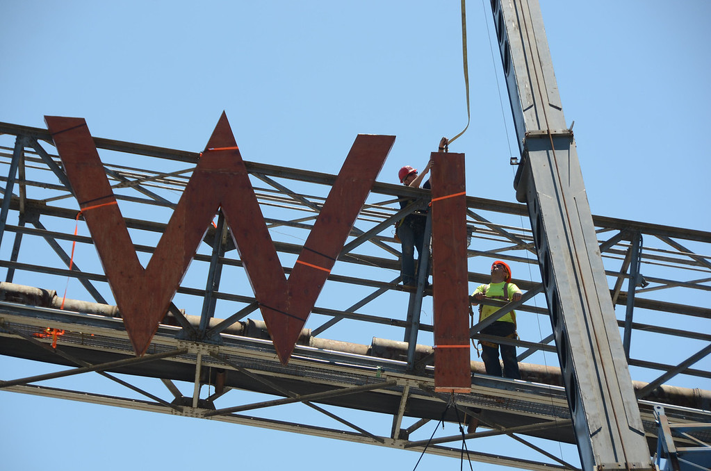 . Derek Parker, left, of the Mass MoCA art fabrication crew and John Dix, right, of Gagne Mechanical of Clarksburg connect the Wilco letters to the old coal conveyer chute on the Mass MoCA campus on Wednesday afternoon in preparation for this week\'s Solid Sound weekend. (Gillian Jones/North Adams Transcript)