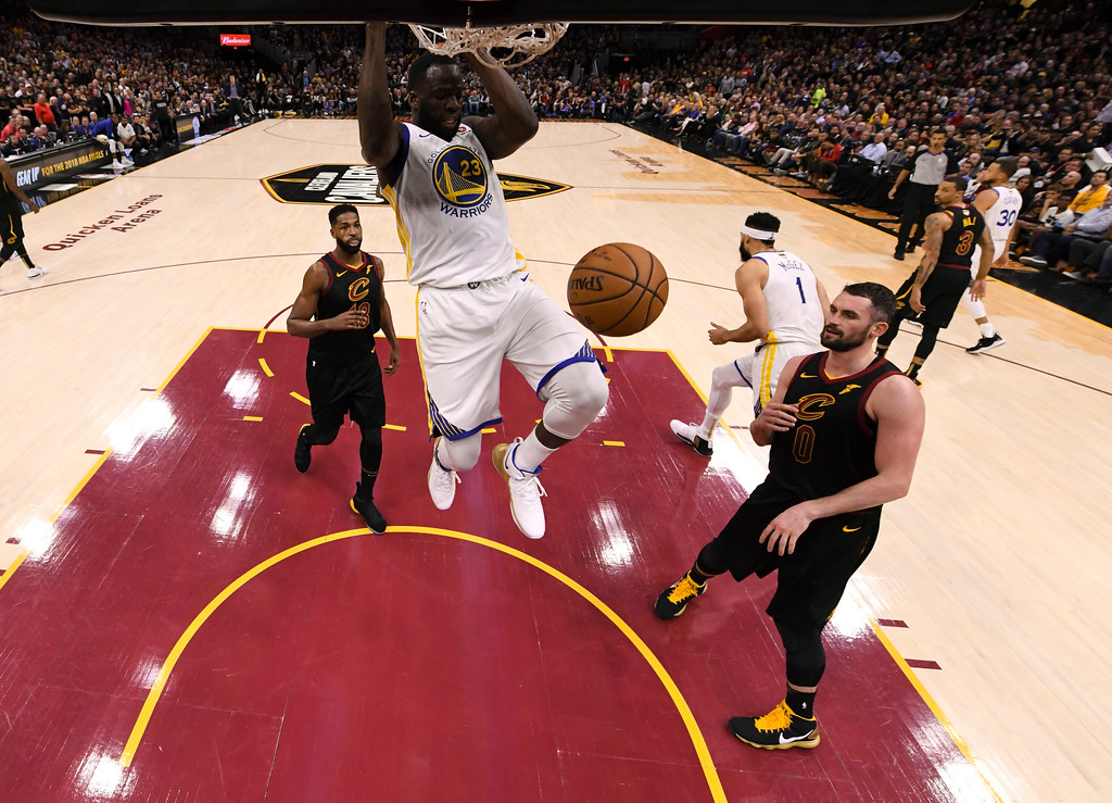 . Golden State Warriors forward Draymond Green (23) follows through on a dunk in front of Cleveland Cavaliers center Kevin Love (0) during the second half of Game 3 of basketball\'s NBA Finals, Wednesday, June 6, 2018, in Cleveland. The Warriors defeated the Cavaliers 110-102 to take a 3-0 lead in the series. (Kyle Terada/Pool Photo via AP)