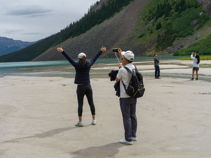 Tourists photographing at lakeside, Lake Louise, Improvement District 9, Banff National Park, Alberta, Canada