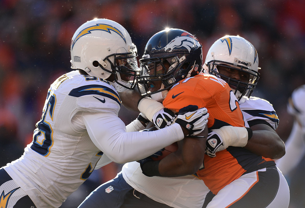 . Denver Broncos running back Knowshon Moreno (27) is tackled by San Diego Chargers inside linebacker Donald Butler (56) and San Diego Chargers defensive end Corey Liuget (94) in the first quarter. The Denver Broncos take on the San Diego Chargers at Sports Authority Field at Mile High in Denver on January 12, 2014. (Photo by Hyoung Chang/The Denver Post)