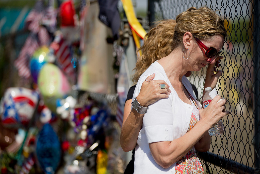 . Linda Lambert is comforted by her friend Margo Williams as she visits the memorial outside the Granite Mountain Interagency Hotshot Crew fire station, Tuesday, July 2, 2013 in Prescott, Ariz. Lambert is the aunt of Andrew Ashcraft, one of the 19 firefighters killed Sunday, by an out-of-control blaze near Yarnell, Ariz. (AP Photo/Julie Jacobson)